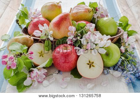 Apple and pears in spring composition with flower, on the wood table with linen tablecloth