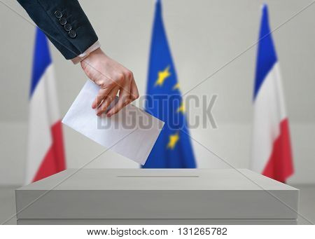 Election In France. Voter Holds Envelope In Hand Above Vote Ball