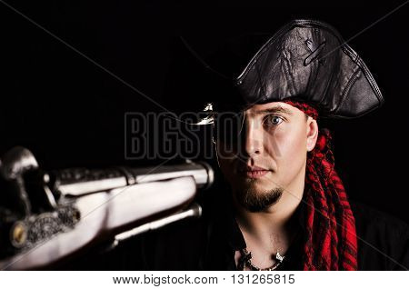 Portrait of a young male pirate with a frightened or surprised look on his face with the barrel aimed at his old gun