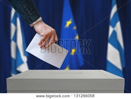 Election In Greece. Voter Holds Envelope In Hand Above Vote Ball