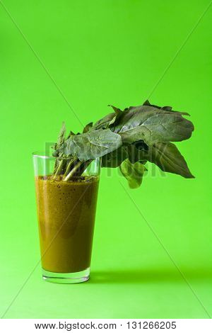 Fresh healthy drink with spinach on green background