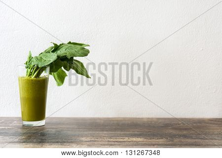 Fresh healthy drink with spinach on rustic wood