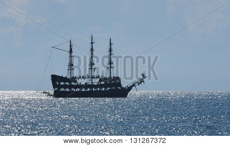Old ancient pirate ship silhouette on the sea.