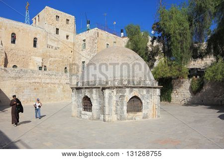 JERUSALEM, ISRAEL - OCTOBER 23, 2010: Dome with barred windows in the old town. Female photographer with equipment and a monk in black robes