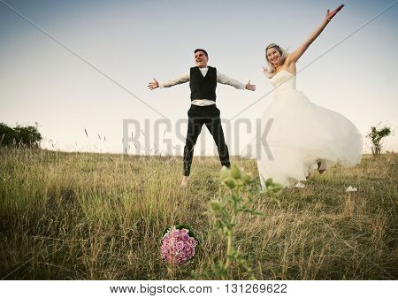 Happy wedding couple jumping for joy in beautiful scenery