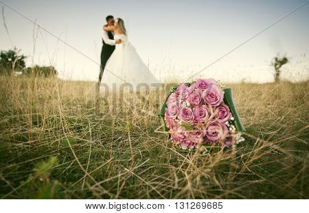 Romantic wedding couple in beautiful scenery - focus on pink wedding bouquet
