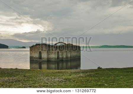 Abandoned destroyed stone orthodox church in dam waters amid cloudy sky background