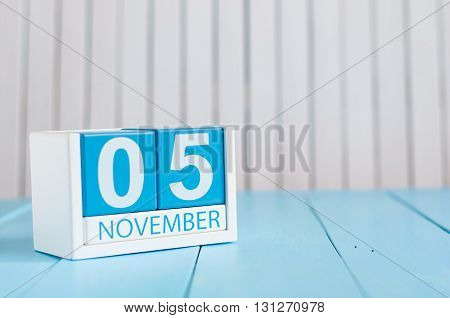 November 5th. Image of november 5 wooden color calendar on blue background. Autumn day. Empty space for text.