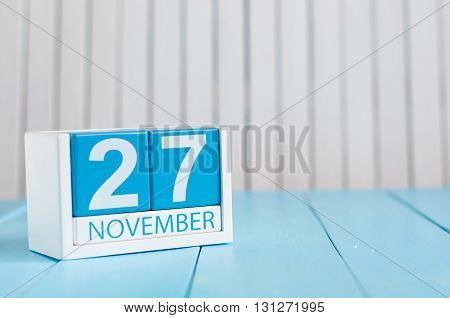 November 27th. Image of november 27 wooden color calendar on blue background. Autumn day. Empty space for text.