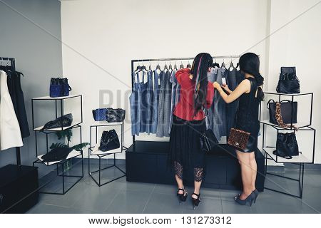 Rear view of female friends looking at dresses on a rack