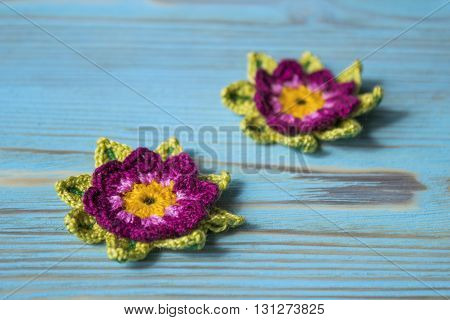 Colorful original crochet handmade background with flowers and leaves, macro photo. Crochet colorful Lotus flowers on wooden colored background