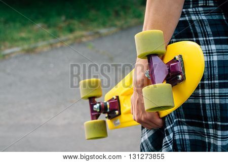 Girl In Jeans And A Plaid Shirt Holding A Yellow Plastic Skateboard With Green Wheels