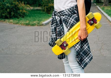Girl In Jeans And A Plaid Shirt Is Walking In The Park With Yellow Plastic Skateboard In Hands