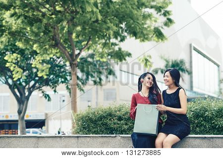 Pretty Vietnamese young women sitting outdoors after successful shopping