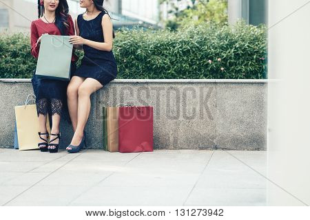 Cropped image of female friends discussing purchases when sitting outdoors