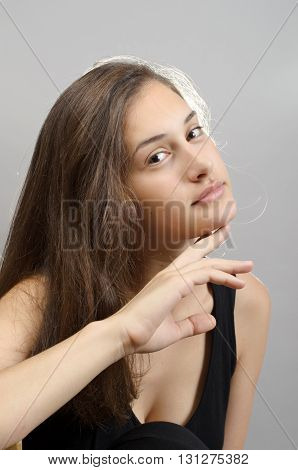 Portrait Of A Beautiful Young Woman Standing Against Grey Background