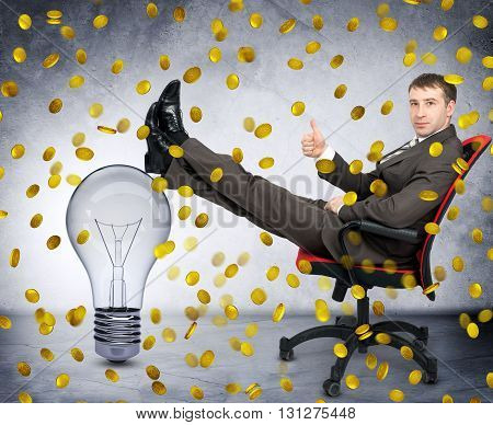 Businessman with light bulb under coin rain, idea is money concept