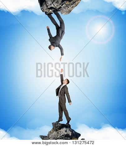 Two businessmen on rocks attracted to each other isolated on blue sky background