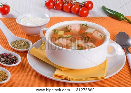 Salmon soup with carrot and potato seasoned with dill in white bowl served on an orange napkin on a white wooden table with cream sauce and spices close-up