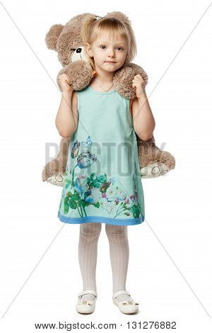 Portrait of a little blonde girl hugging a teddy bear toy isolated on white background