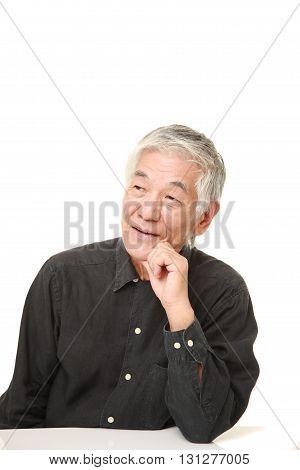 studio shot of senior Japanese man thinks about something on white background