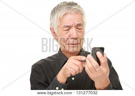 senior Japanese man using smart phone looking confused