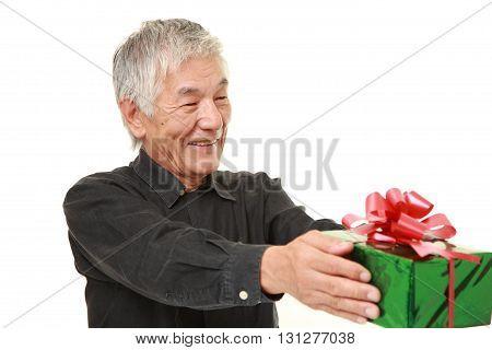studio shot of senior Japanese man offering a gift on white background