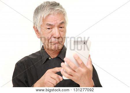 senior Japanese man using tablet computer looking confused
