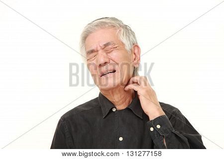 studio shot of senior Japanese man scratching his neck on white background