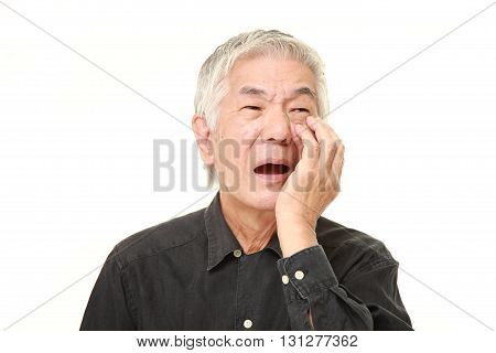 studio shot of senior Japanese man suffers from toothache on white background