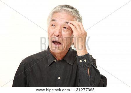 studio shot of senior Japanese man has lost his memory on white background