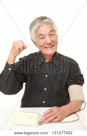 studio shot of senior Japanese man checking his blood pressure on white background