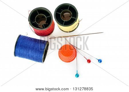 Spools of different threads, thimble and needles isolated over the white background, as sewing composition