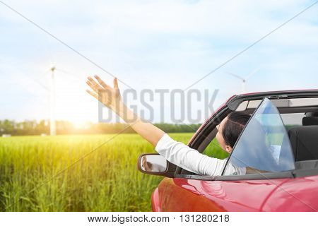 Woman in a red cabriolet in a field at sunset, raises her arms up. Travel concept.