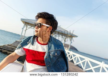 young asian handsome man standing and smile with jean jacket at Asdang bridge on sea background Thailand