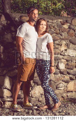 Young Beautiful Stylish Couple Sitting Near Big Stone Wall