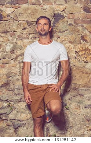 Handsome Masculine Man Leaning Against Stone Wall Outdoors