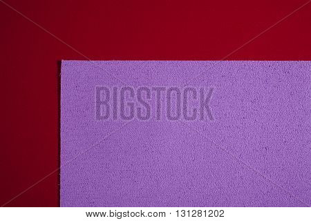 Eva foam ethylene vinyl acetate sponge plush bright purple surface on red smooth background