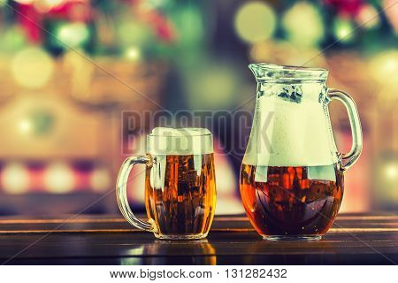 Beer. Two beers on wooden table in pub hotel or restaurant. Jug and cup beer.