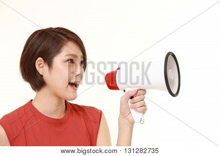 studio shot of young Japanese woman with megaphone