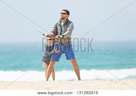 family of father and son playing with kite at the beach being active and happy enjoying vacation together vacation and lifestyle concept