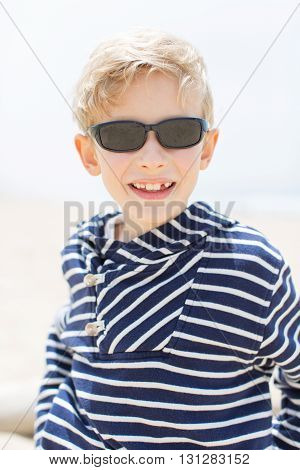 portrait of smiling happy boy in sunglasses at the beach enjoying summer vacation