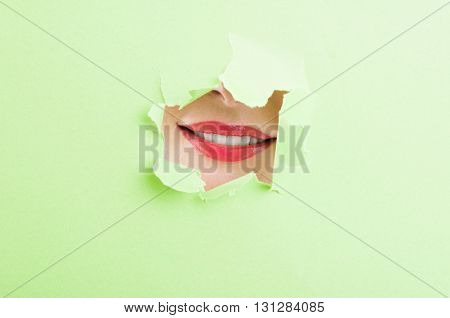 Beautiful Female Mouth Showing A Smile Thru Ripped Cardboard