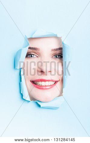 Pretty Female With Perfect Skin Smiling Thru Torn Cardboard