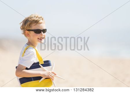 portrait of smiling happy boy in sunglasses holding beach bag and starfish enjoying summer vacation copyspace on the side