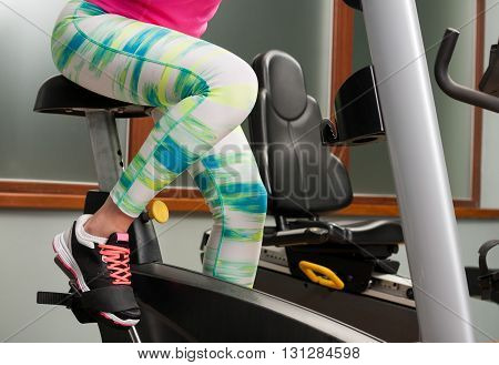Young Woman Sitting And Cycling On Stationary Bike
