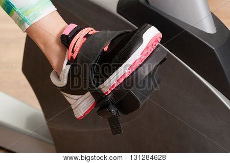 Closeup Of Young Woman Feet Stand On Stationary Bike Pedal