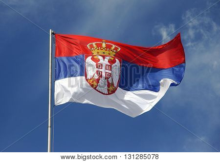 Serbian flag waving in windy day against blue sky