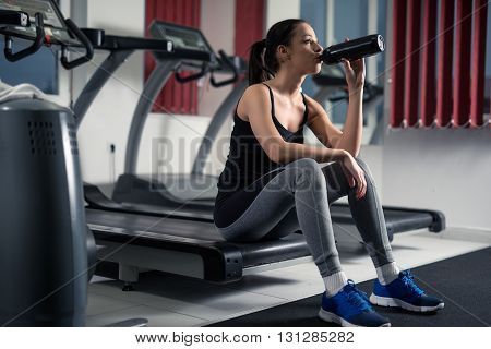 Young woman sitting on a machine in the gym and drinking some water.
