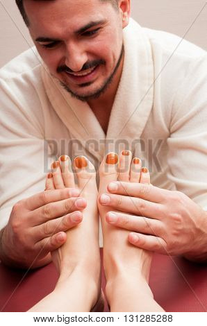 Attractive Masseur Smiling And Massaging Woman Feet And Soles